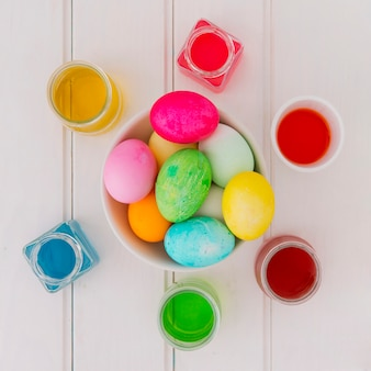 机の上の染料の液体の缶の間のボウルに明るいイースターエッグ