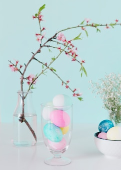 Bright easter eggs near flower twig in vase with water and bowl