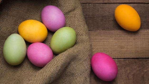 나무 테이블의 배경에 삼 베의 거친 질감에 밝은 부활절 달걀.