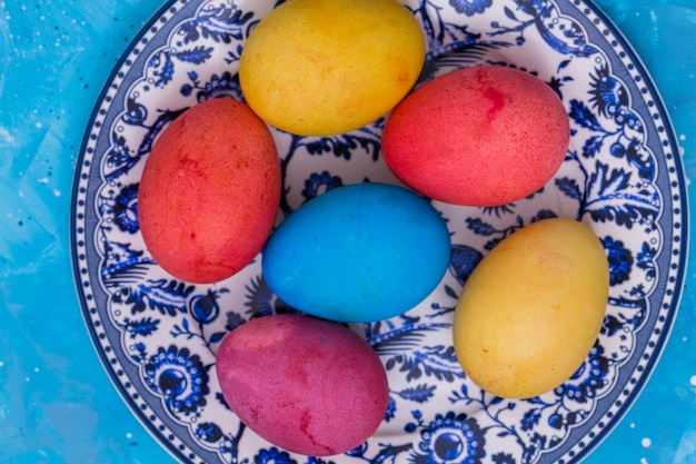 Bright easter eggs on plate on blue table