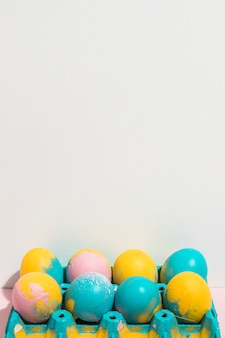 Bright easter eggs in rack on table