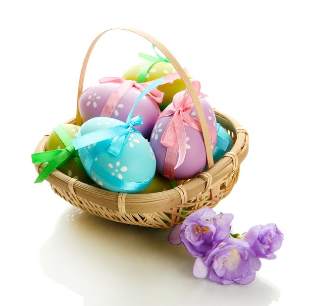 Яркие пасхальные яйца с бантами в корзине, изолированные на белом