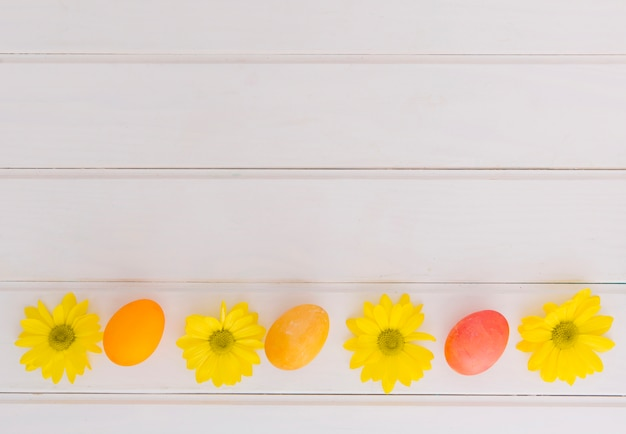 Bright easter eggs and yellow flowers on desk