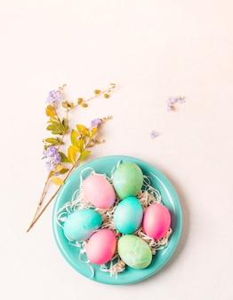 Uova luminose sul piatto vicino al ramoscello di fiore