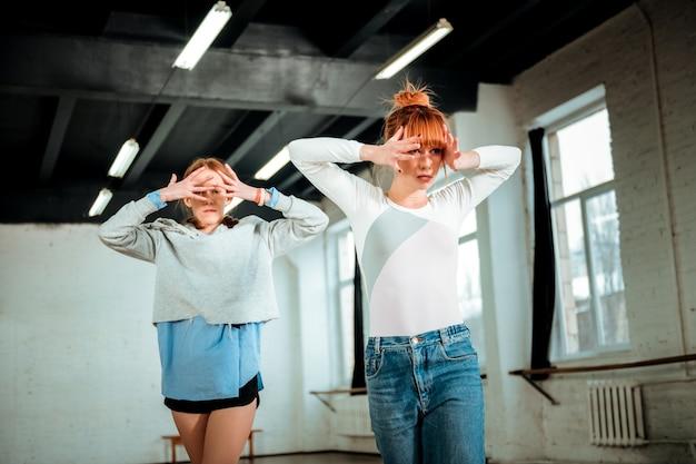 Яркие эмоции. красивая рыжая учительница в синих джинсах и студентка в черных шортах выглядят артистично