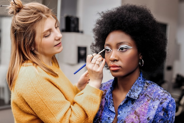 Bright eyelids. fair-haired young stylist with black nail polish looking creative while putting silver eyeshadow on models eyelids