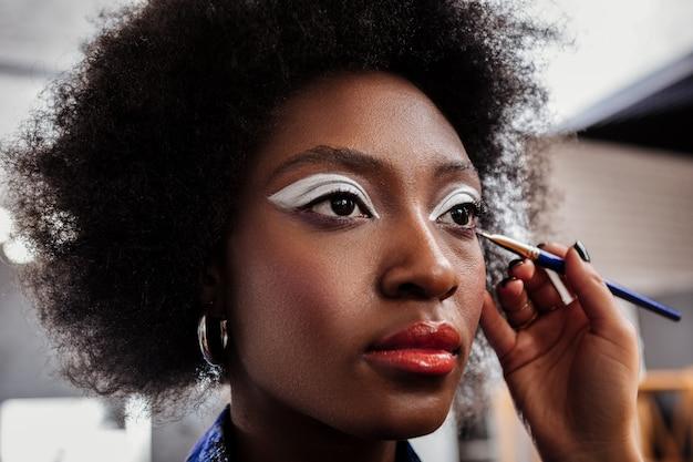 Bright eyeshadows. dark-skinned model with bright eyeshadows looking thoughtful while sitting