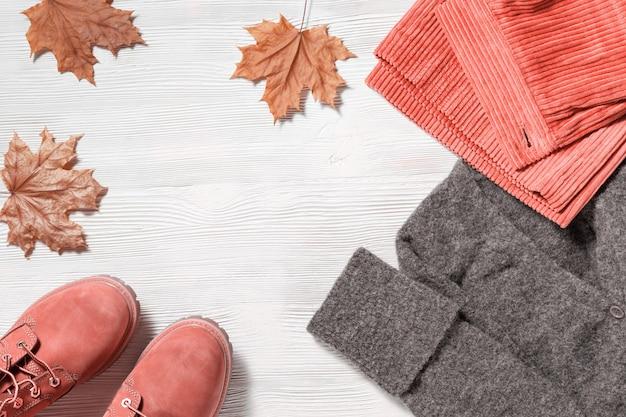 女性のための明るいファッション服。秋のフラットは暖かい服装で横たわっていた。コーデュロイのパンツ、ウールグレーのニットジャンパー、コンフォートレザーブーツ。