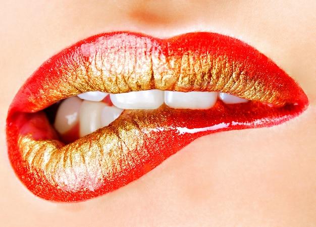 Яркий модный золотисто-красный макияж человеческих губ