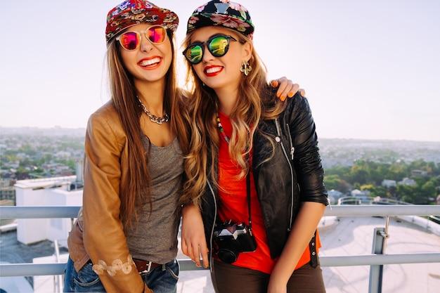 スタイリッシュな盗品の帽子、革のジャケットとサングラスを身に着けて、笑いながら一緒に楽しんでいる2人のかわいい姉妹の明るいファッションアウトドアライフスタイルの肖像画。屋根でポーズをとる最高の悪鬼
