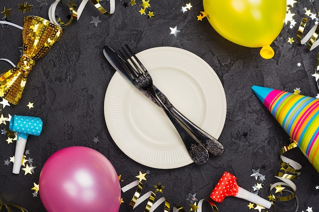 Bright festive carnival table setting with plate and cutlery on black stone table decorated with party accessories