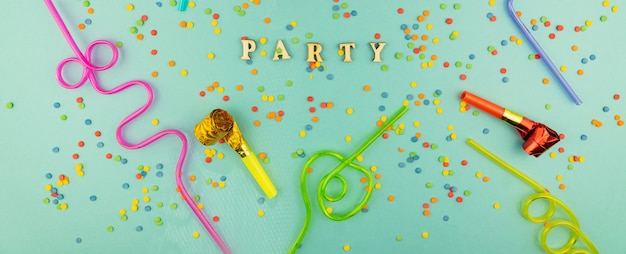 Bright festive party background - cocktail straws and party whistles with scattered sugar sprinkles.