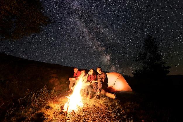 夜のキャンプ中に明るい火と4人の幸せな人々が星が散らばって空を背景にその近くのログに座っています。