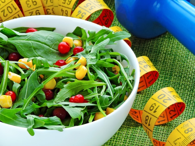 Bright fitness salad with arugula corn and cowberry in a white bowl.