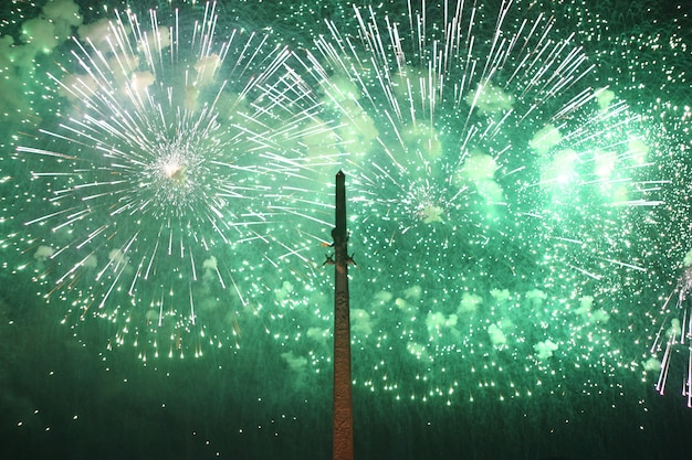 Bright flashes of green fireworks in the sky. the concept of the holiday