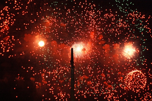 Bright flashes of red fireworks in the sky. the concept of the holiday