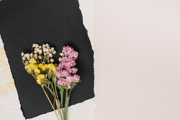 Bright flowers branches with black paper on table