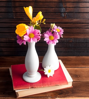 Bright flowers in two vases on book