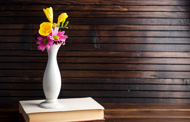 Bright flowers in vase on book