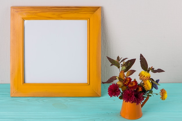 Bright flowers in vase near frame on table
