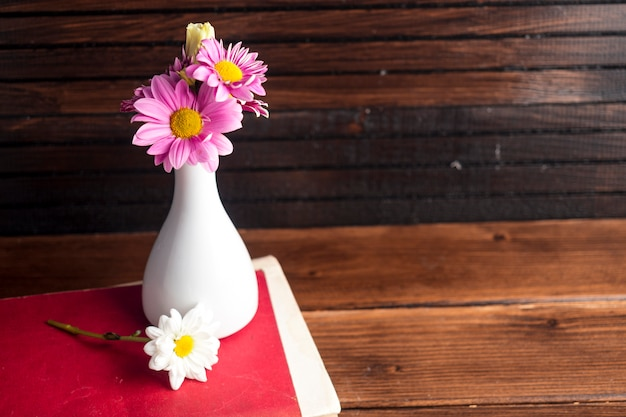 Bright flowers in white vase on book