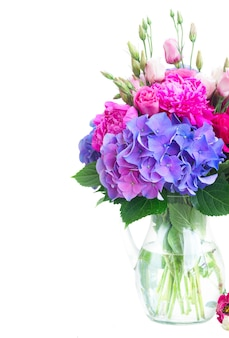 鮮やかな新鮮なピンクの牡丹、トルコギキョウ、花瓶の青いオルテンシアの花の花束は、白で隔離のクローズアップ