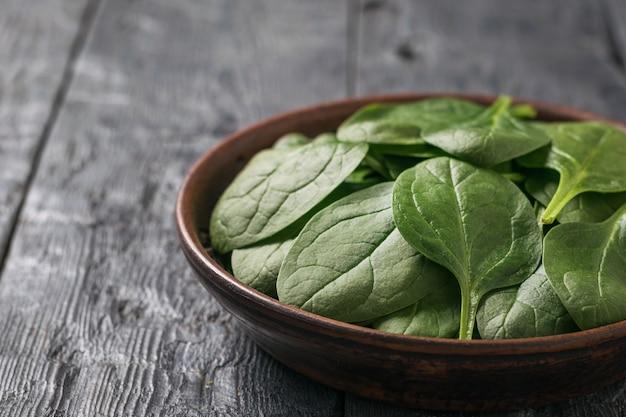 밝고 신선한 시금치는 나무 테이블에 있는 점토 그릇에 나뭇잎. 건강을 위한 음식. 채식주의 자 음식.