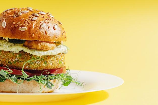 グルテンと肉を含まない明るく新鮮なベジーバーガー。白いプレートの黄色い表面にハンバーガー
