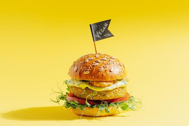 グルテンと肉を含まない明るく新鮮なベジーバーガー。黄色い表面のハンバーガー