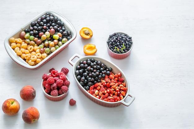明るく新鮮な野生のベリーと桃の孤立した上面図。健康的な食事の概念。