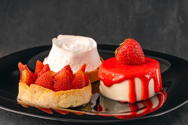 Яркие фруктовые пироги на черной тарелке. фруктовые десерты со свежей клубникой. аппетитные кондитерские изделия.
