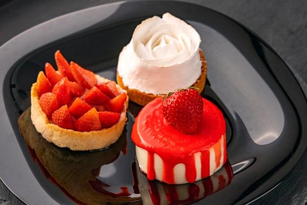 Яркие фруктовые пироги на черной тарелке. фруктовые десерты со свежей клубникой. кондитерские изделия. красивые кондитерские изделия.
