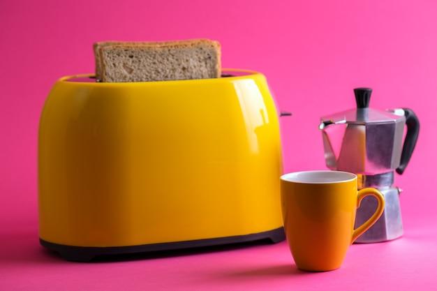 明るく楽しい朝食。ピンクの背景に黄色のトースターと一杯のコーヒー