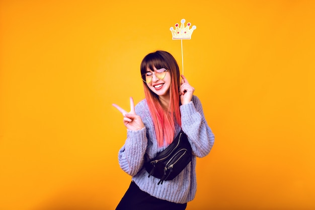Bright funny portrait of cheerful hipster woman with bright pink hair, wearing cozy sweater, holding fake party crown and smiling, ready for party, yellow wall.