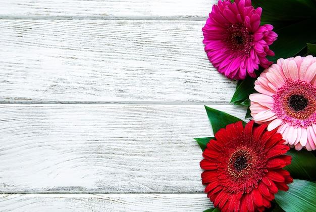 白い木製のテーブルに明るいガーベラの花。花のフレーム、上面図
