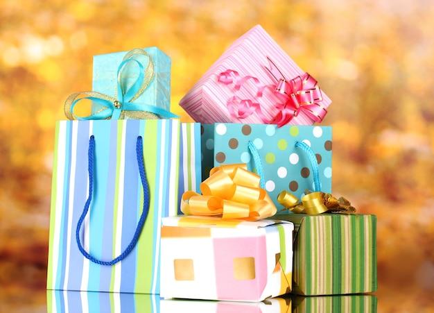 Яркие подарочные пакеты и подарки на желтом фоне