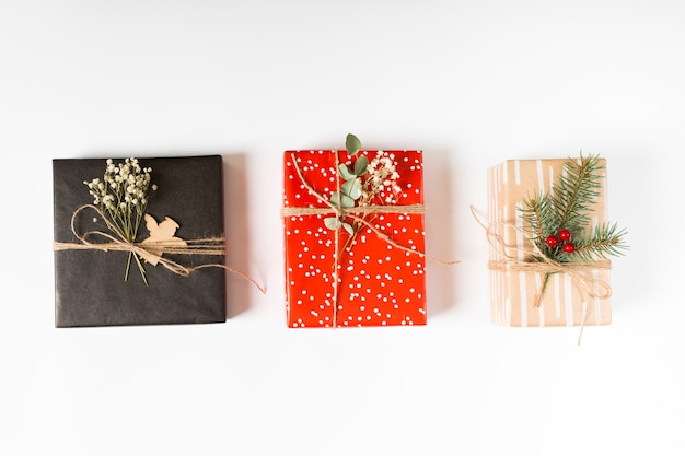 Bright gift boxes with branches on table