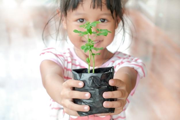 明るい女の子と苗は植える準備ができています。