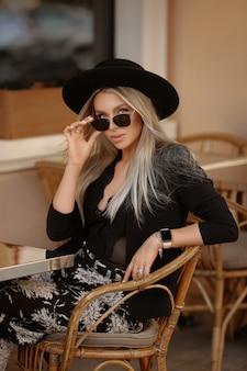 Яркая девушка со светлыми волосами и в летний наряд сидит в кафе на улице в летний день.