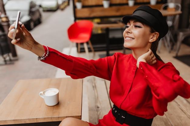 Яркая девушка с шикарным макияжем, одетая в шелковое платье, которое дополняет модные аксессуары, делает селфи по телефону на размытой улице