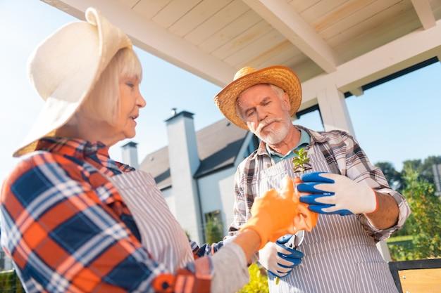 Яркие перчатки. пенсионеры, симпатичные сияющие мужчина и женщина в ярких перчатках сажают цветы