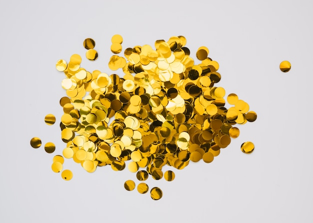 Bright golden confetti on white background