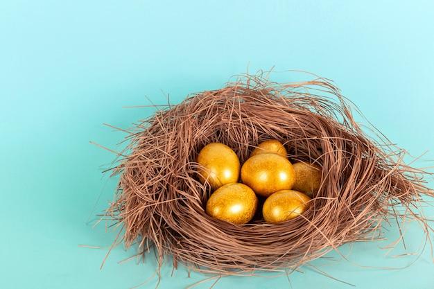 青い背景の上のわらの巣の明るい金色のイースターエッグ。
