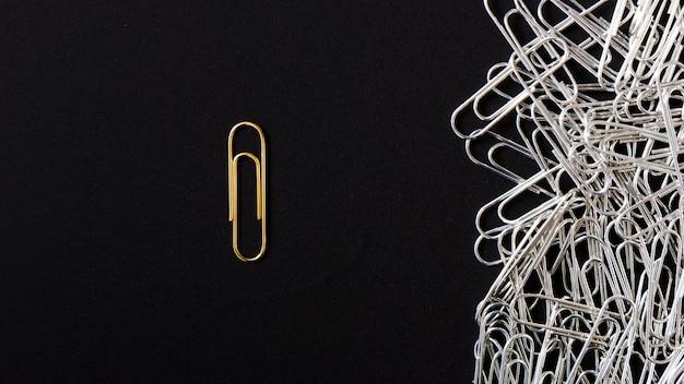 Яркая золотая скрепка, стоящая из серебряных клипов на черном фоне