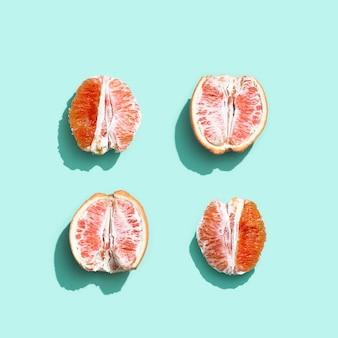 Яркий грейпфрут или красный апельсин на пастельно-бирюзовом фоне.