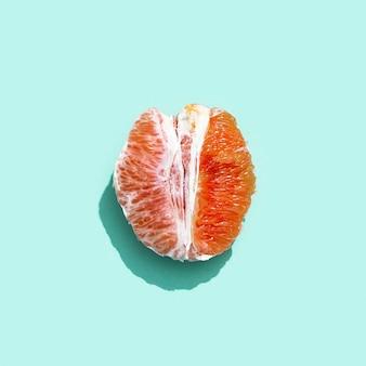 파스텔 청록색 배경에 껍질이없는 밝은 자몽 또는 레드 오렌지 최소한의 과일과 여름 개념