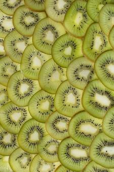 ジューシーなキウイのスライスと明るい緑の背景。健康食品の背景。