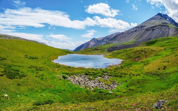 日光の下で高原の谷の山の湖と青い曇り空の下の大きな山と明るい緑青高山の風景。緑の山の谷の雲の影。パノラマビュー。
