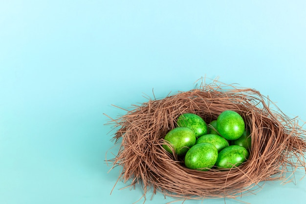 青い背景の上のわらの巣の明るい緑のイースターエッグ。イースター、おめでとう