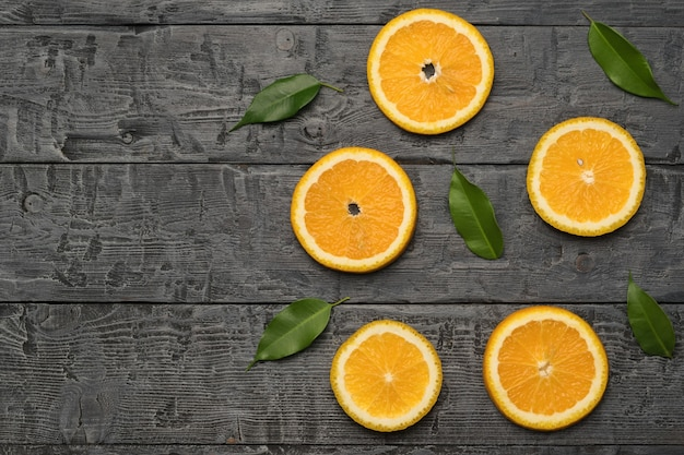 Яркие зеленые листья и дольки апельсина на черном деревянном столе. место для текста. плоская планировка.